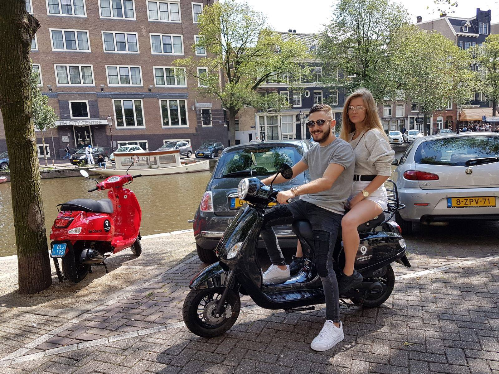 A couple driving a rented scooter in Amsterdam